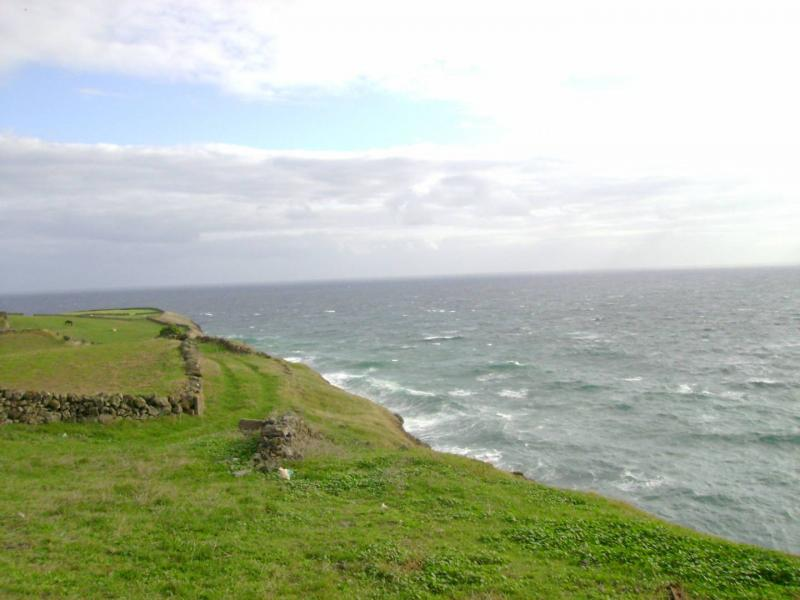 The images shows a spooky place in Portugal. It is a cliff in the Azores. We can see on the left green grass fields and on the right there is the endless ocean. On top the is the sky, cloudy, but with some sun.