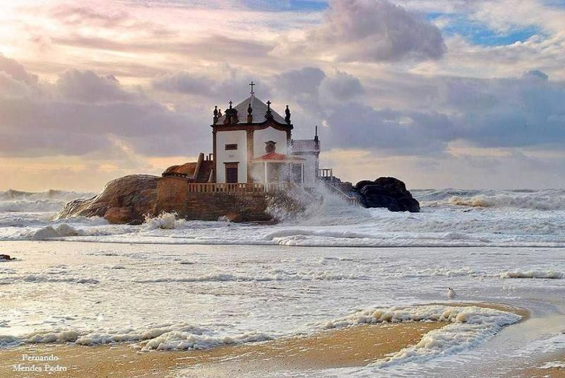 The picture shows an abandoned chapel on top of a rock, surrounded by the ocean. This is a spooky place in Portugal. The weather is very cloudy with some rays of sun coming out through the clouds. The sea ir very agitated.