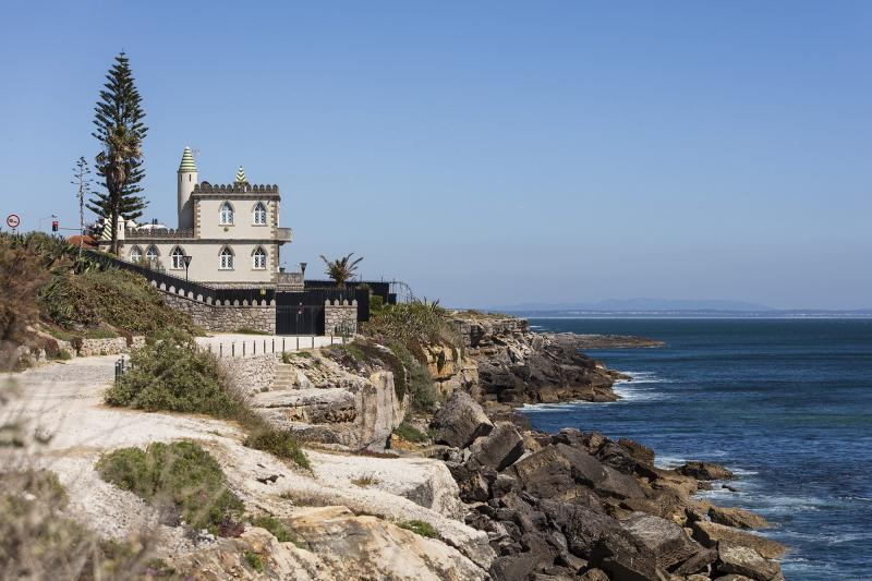 The picture shows a spooky place in Portugal. This one is a small castle in the coast of Estoril. On the left we see the building on the left speared by the sea through a sidewalk and rocks. The weather is a clear sky with a lot of sunlight.