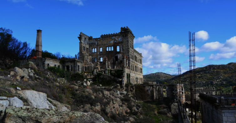 The image shows a spooky place in Guarda. An abandoned and ruined building in the middle fo the picture, on top of rocks and nature surroundings. The building is old and neglected, empty window openings and broken glass.