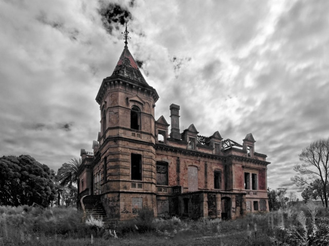 The image shows a spooky place in Portugal. This is Palácio Marques Gomes in Gaia. The image shows the palace in color and the surroundings in black and white. The weather is very cloudy.  Around the palace there is only nature, trees and low greens. The palace is in red brick and looks scary and abandoned. There are window openings without glass on it. The palace has a tower in the left front corner.