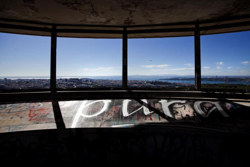 The image shows a spooky place in Lisboa. There is a panoramic view over Lisbon and the Tagus River. We look into it through four glass-less window openings and a tiled illustration of Lisbon's most iconic buildings is below the openings. The weather is sunny and clear sky.