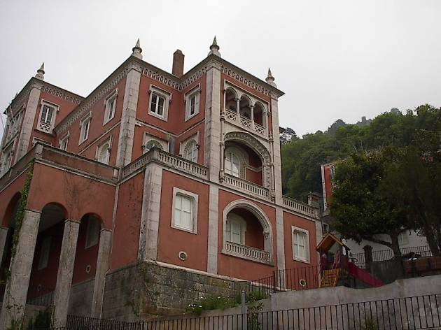 The image shows a spooky place in Portugal. There is a palace seen from down up, from the street. The palace is in a dark pink-reddish color, with corners in limestone. The weather is cloudy.
