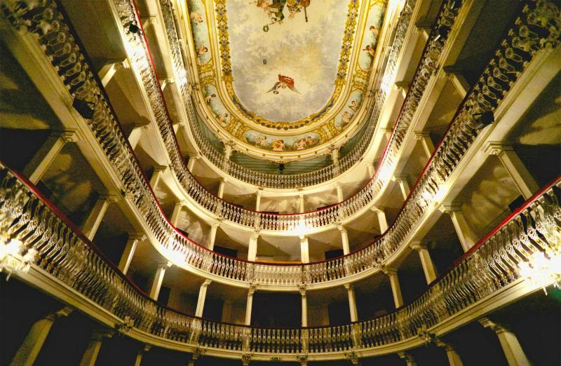 The image shows a spooky place in Portugal. There a theatre. A view from the bottom to the top of the galleries. There are four galleries. And the ceiling painted in fresco.